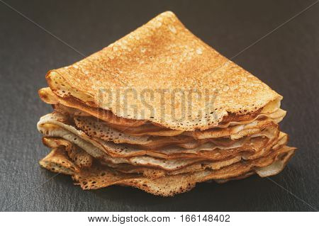 thin crepes or blinis folded in triangles on slate board, vintage toned