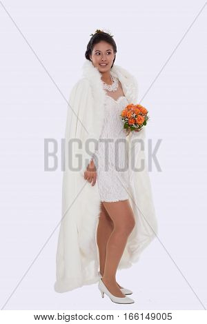 Young bride in short dress with white cape and bridal bouquet of roses in hand