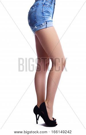 Beautiful woman legs in high heel shoes and jeans shorts. Smooth skin with clean depilation.