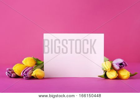 Bouquet Of Tulips With Sheet Of Blank Paper On Pink Background