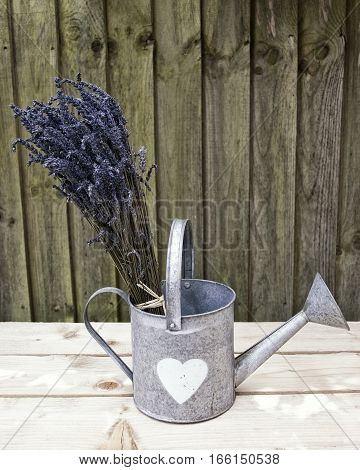Bunch of lavender in a tin watering can on a wooden surface with wood in the background. Bleach effect an space for text.