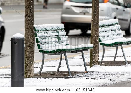 Empty chairs covered with snow in winter on a side street in the city of Lucerne.