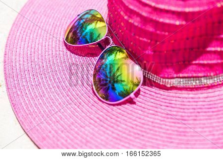 Pink summer hat and colorful sunglasses with palm tree reflection