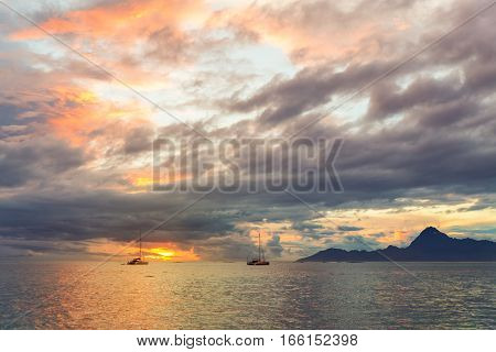 Dramatic sunset and far yachts in the sea