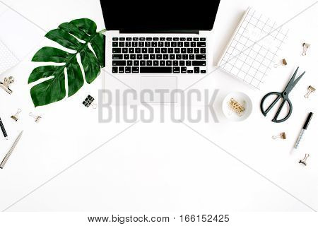 Home office workspace with laptop palm leaf notebook and accessories. Flat lay top view