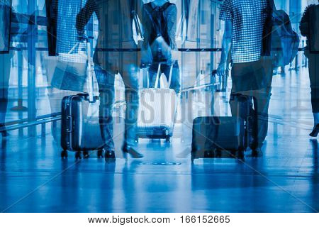 Blurred image of people walking in a busy airport in Shanghai China, toned blue.