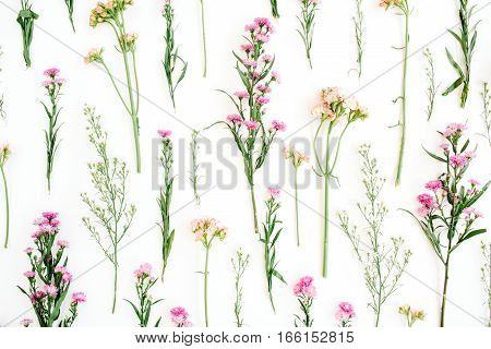 Floral pattern with pink and beige wildflowers green leaves branches on white background. Flat lay top view. Valentine's background