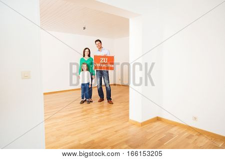 family in an empty apartment, holding 'zu verkaufen' for sale sign