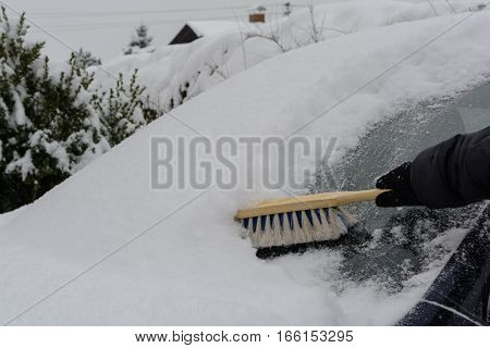 Remove the snow from the windscreen with hand brush - close-up