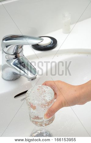 Filling a glass with water under the tap
