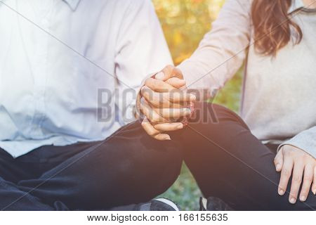 Young couple holding hands in garden valentine day.