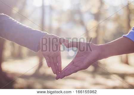 blur hands of couple make heart symbol in garden with sunlight valentine day.