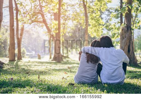 Valentine couple sit on grass in garden while sunset.