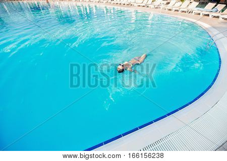 young woman with swimsuit swimming on a blue water pool