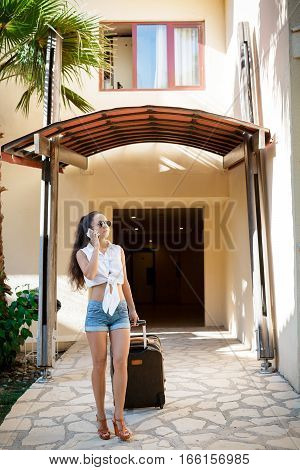 young woman in sunglasses, white shirt and shorts with suitcase and smartphone