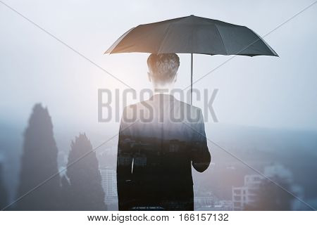 businessman with umbrella looking on city. Close up.