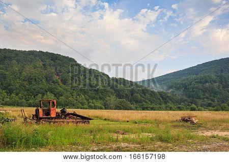 Abandoned dozer stands on wild mountain background