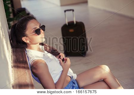 young woman in sunglasses with a suitcase sits and waits