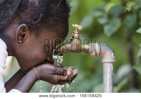 Clean Fresh Water Scarcity Symbol: Black Girl Drinking from Tap. Young African girl drinking clean water from a tap. Hands with water pouring from a tap in the streets of the city Bamako, Mali.