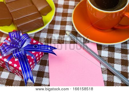 Sheet Notes, Gift And Chocolates With A Cup Of Coffee On The Table. Checkered Background