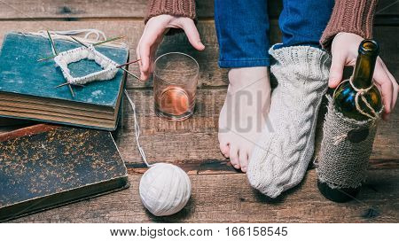 Feet and hands of person wearing one winter sock, knitting the other one and drinking wine