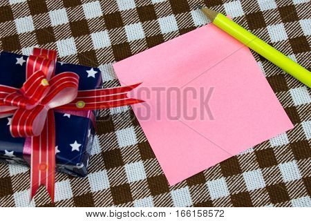 Pink Piece Of Paper For Notes, Pencil And Gift On Table, Close-up. Checkered Background