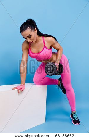Muscular woman in pink leggings, top and gloves training with dumbbells. Isolated