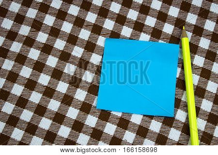 A Blue Piece Of Paper For Taking Notes With A Pencil On The Table, Top View. Checkered Background