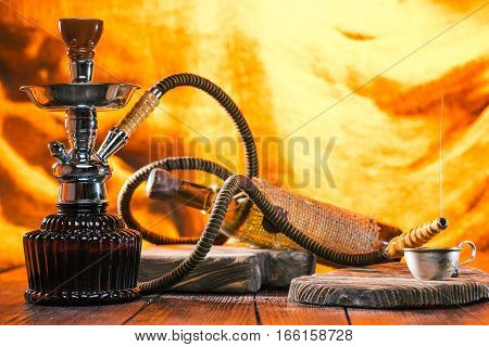 Hookah and wine. Coffee cup on serving board. Hot light background