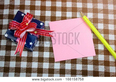 Pink Piece Of Paper For Notes, Pencil And Gift On Table, Top View. Checkered Background