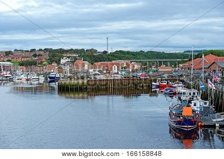 WHITBY, ENGLAND - JUNE 30, 2016: The harbor in the port of Whitby on the North Yorkshire coast. Tourism started in Whitby during the Georgian period and developed further on the arrival of the railway in 1839.