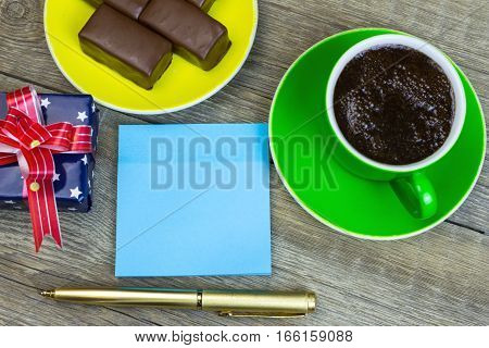 Blue Piece Of Paper For Notes, Pen, Chocolates On A Saucer And Coffee Cup On Old Wooden Table