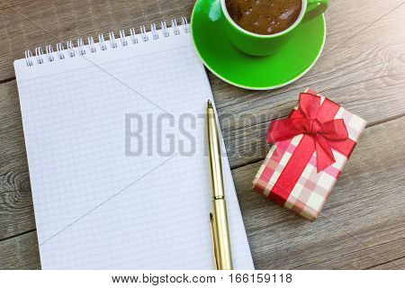 Clean Sheet Of Notebook With A Pen, Coffee Cup And Gift On Wooden Table