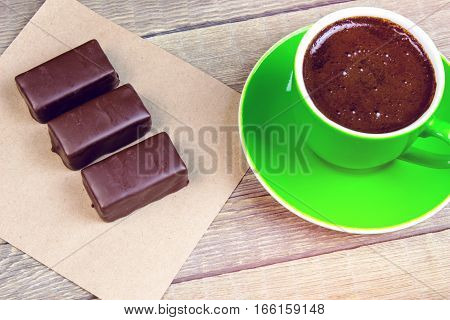 A Few Chocolates On A Piece Of Paper With Coffee Cup On Wooden Table