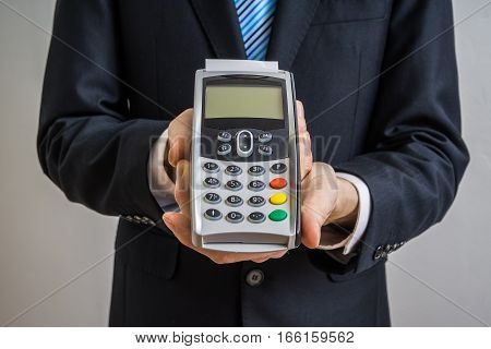 Businessman holds payment terminal in hands for paying with credit card.