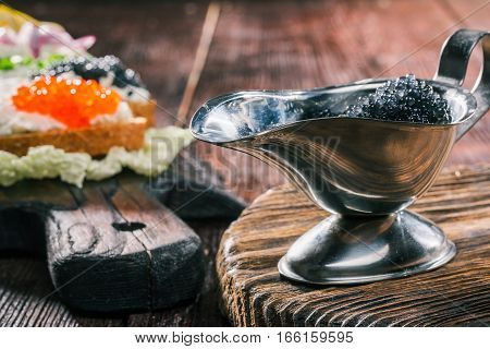 Caviar and toasts of bran bread with cottage cheese spread. Natural wood board serving