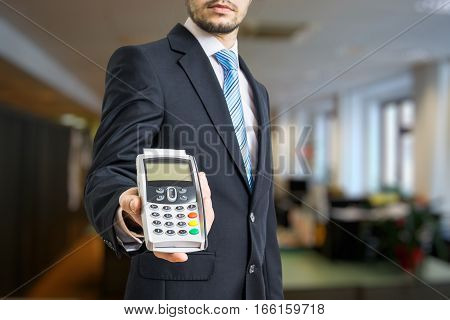 Businessman is offering payment terminal for paying with credit card in office.