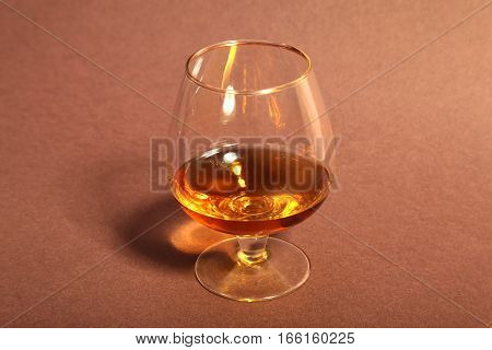 cognac in a glasses, pralines on Old textile sacking.