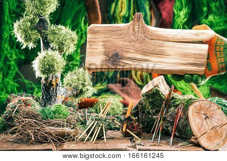 Wood board for sign of yarn and needle shop. Decorative forest of yarns and knitting tools on the background