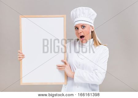 Portrait of excited and surprised female chef holding whiteboard .