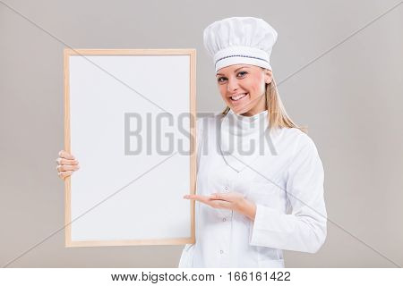 Portrait of beautiful female chef showing whiteboard on gray background.