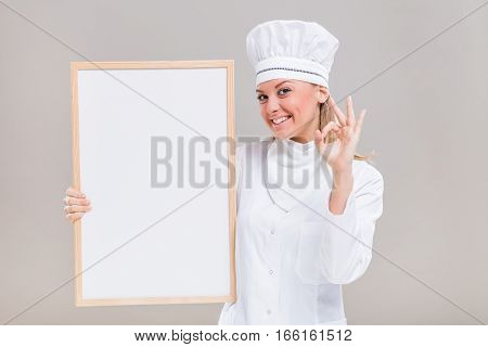 Portrait of beautiful female chef showing ok sign while holding whiteboard on gray background.