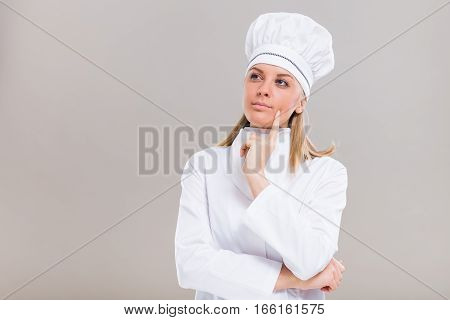 Beautiful female chef is thinking what to cook.