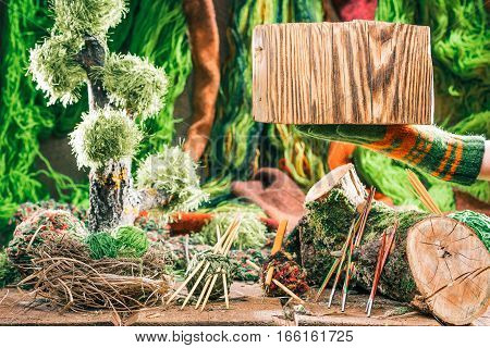 Wood stump on hand for sign of yarn shop. Decorative forest of yarns and needles on the background