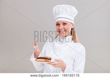 Beautiful female confectioner is showing slice of cake on gray background.