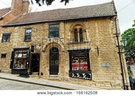 LINCOLN, UK - JULY 1, 2016: Small shops on Steep Hill a popular tourist street in the historic city of Lincoln. In 2011 it was named