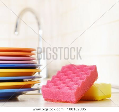 Several Plates And A Kitchen Sponge. Dishwashing Concept