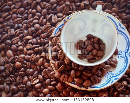 Coffee cup from thin porcelain against the background from coffee grains.