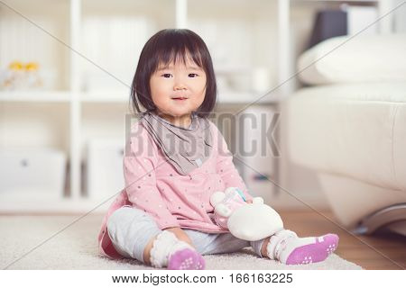 Happy Little Japanese Girl Playing On White Capet At Home