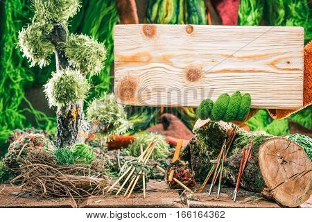 Rectangle wooden board for sign of yarn shop. Decorative forest of green yarns, samples and knitting tools on the background